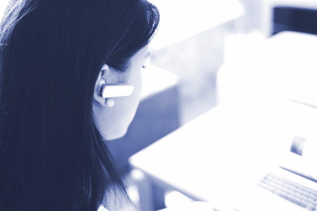 Symbolbild für Leads konvertieren: Frau mit einem Headset von hinten