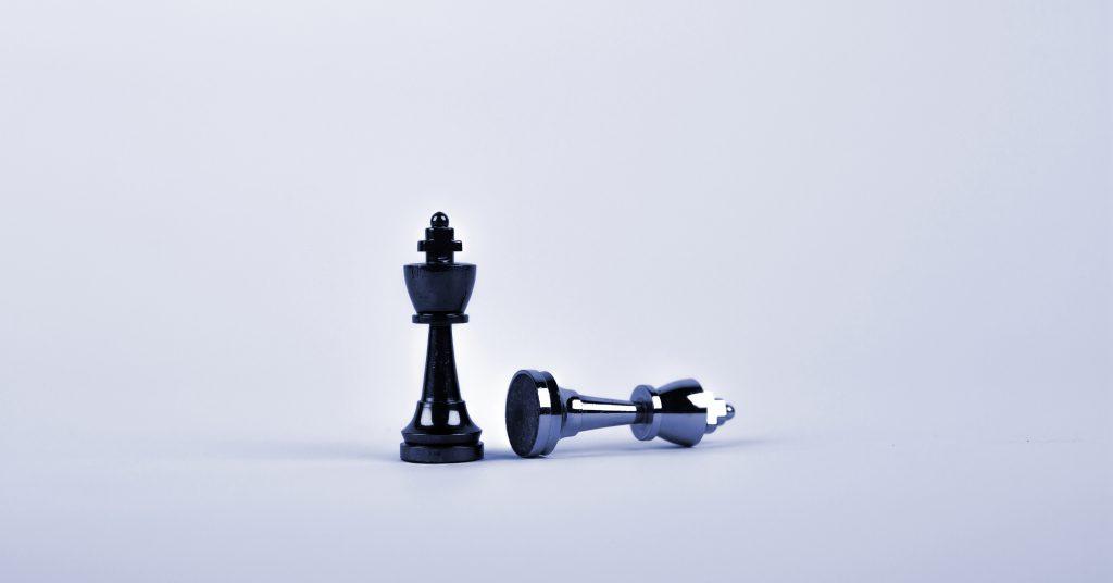 Symbolbild für Intent-Marketing: zwei Schachfiguren, von denen eine steht und eine liegt